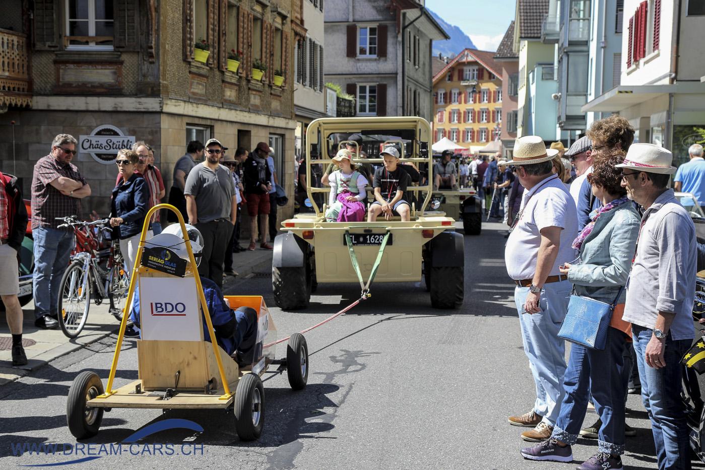 Eine Seifenkiste wird von einem Croco-Geländewagen durch Sarnen gezogen