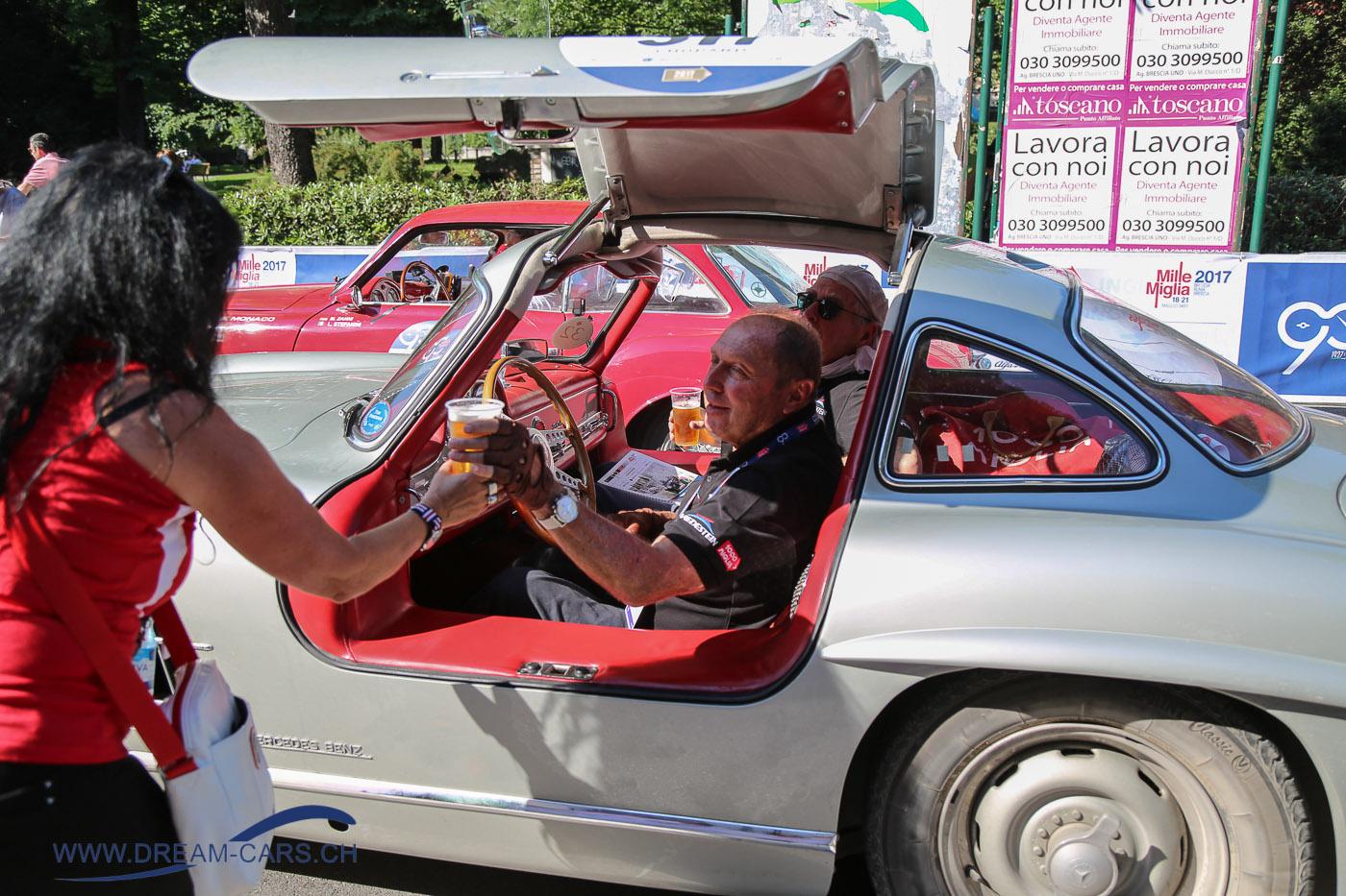 Mille Miglia 2017, 4. Tag, Etappe Parma - Brescia. Die Ärzte sagen ja immer, man solle viel trinken und Jochen Mass wusste das von Ela Lehmann überreichte kühle Bier sehr zu schätzen.